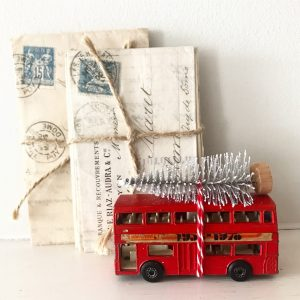 Charmingly shabby vintage toy bus with bottle brush tree
